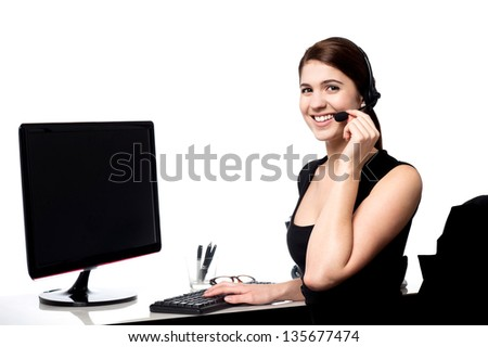 Young pretty female support staff attending clients queries. - stock photo
