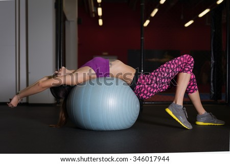 Young pretty fitness woman on a fit ball