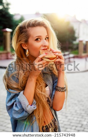 Young pretty funny blond girl eats hamburger fast food sandwich on the street - stock photo