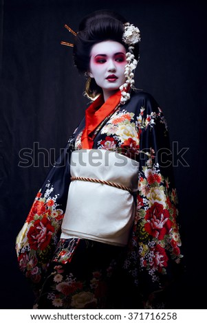 young pretty geisha in kimono with sakura and decoration - stock photo