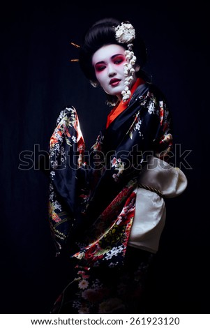young pretty geisha in kimono with sakura and decoration on black background - stock photo