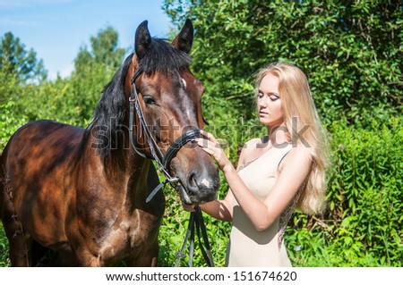 Young pretty girl and a horse - stock photo
