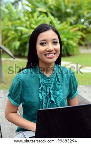 young pretty girl businesswoman using laptop in nature