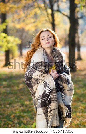 Young pretty girl covered in plaid in autumn day in the park - stock photo