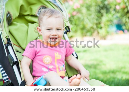 Young pretty girl in a baby carriage outdoor. - stock photo
