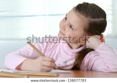 young pretty girl in a pink sweater drawing at the table at home