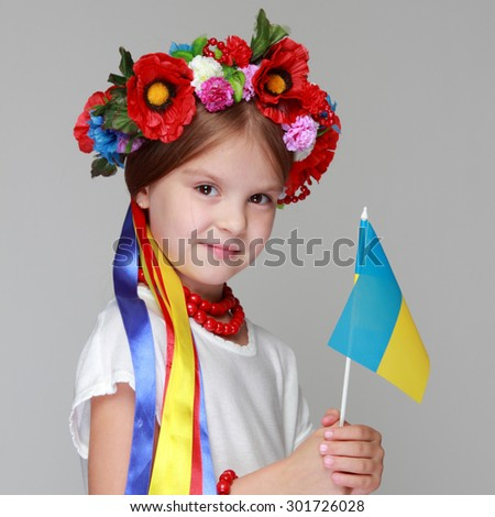 Young pretty girl in a ukrainian national costume on a light background - stock photo