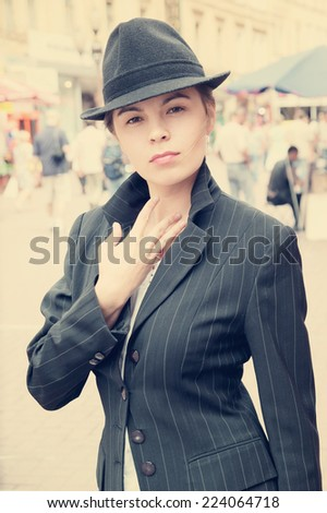 Young pretty girl in hat and jacket in the street  - stock photo