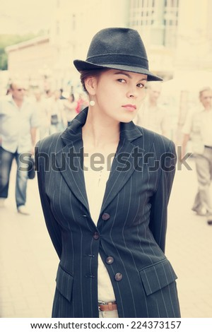 Young pretty girl in hat and jacket in the street