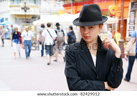 Young pretty girl in hat and jaket in the street - stock photo