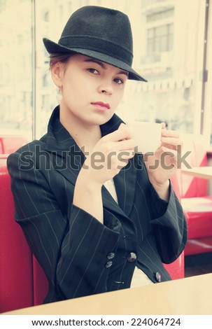 Young pretty girl in hat at the street cafe - stock photo