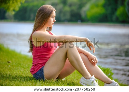 Young pretty girl is relaxing in city park at river shore - stock photo