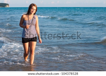 young pretty girl looking at camers and smiling with the sea as a background