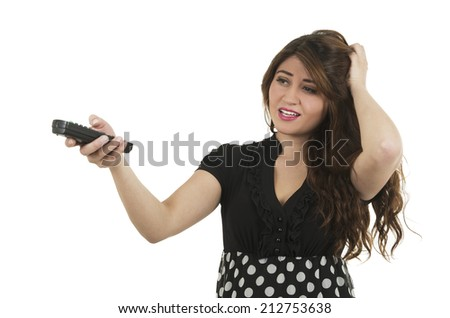 Young pretty girl looking unsure holding remote control isolated on white - stock photo