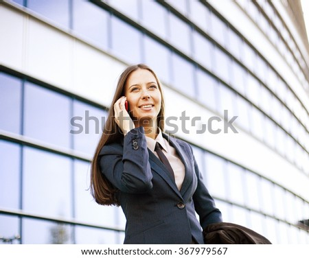 young pretty girl near business building walking, student in america or europe close up smiling
