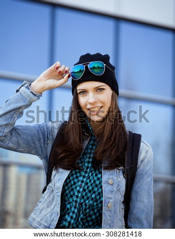 young pretty girl near business building walking, student teenager on blue - stock photo
