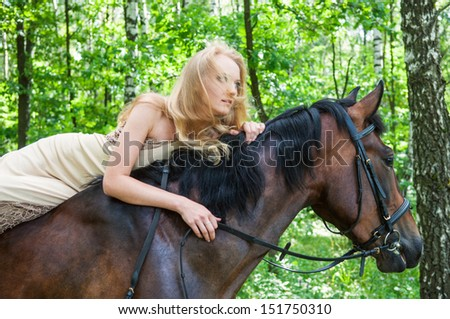 Young pretty girl on horseback in the forest - stock photo