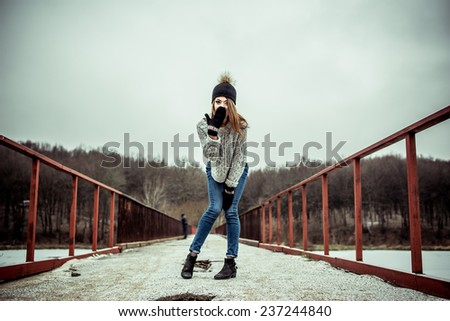Young pretty girl on the bridge with forest and lake on background