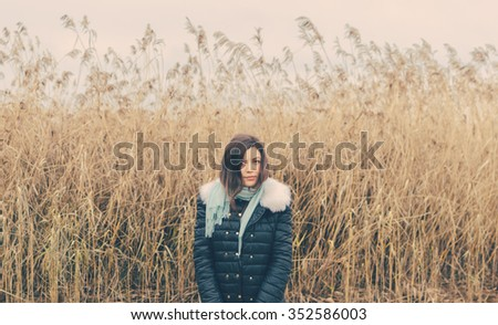 Young pretty girl on the lake in autumn day