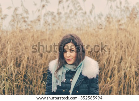 Young pretty girl on the lake in autumn time - stock photo