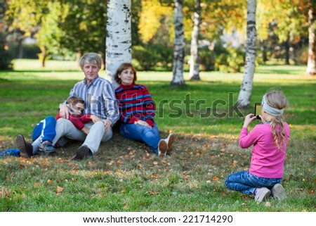 Young pretty girl photographing her family by phone in autumn park - stock photo