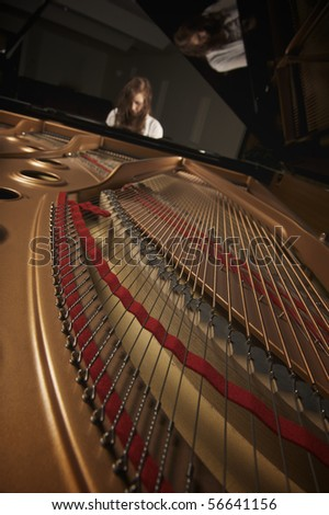 Young pretty girl playing piano in indoor concert hall - stock photo