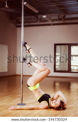 young pretty girl pole dancing in a dance hall - stock photo