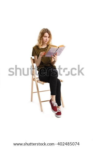 Young pretty girl reads book sitting on a chair isolated. White background - stock photo