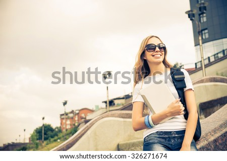 Young pretty girl student at river front with tablet pc in hands