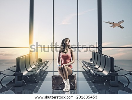 Young pretty girl traveler at airport sitting on suitcase