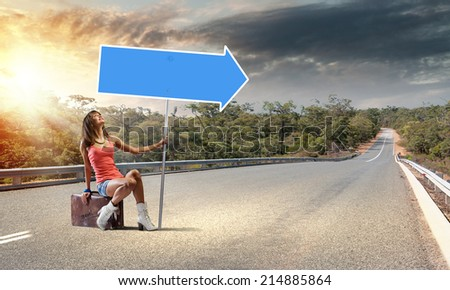 Young pretty girl traveler sitting on suitcase aside of road - stock photo
