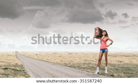 Young pretty girl with her retro suitcase on shoulder