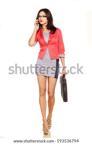 young pretty girl with laptop bag walking on white background - stock photo