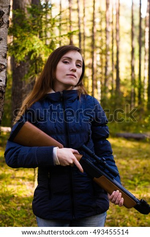 Young pretty girl with rifle in forest