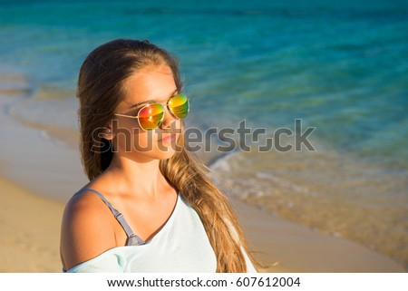 Young pretty girl. Young smiling woman outdoors portrait. Close. ocean. Happy beach  woman living a healthy lifestyle. Beautiful young girl In sunglasses with hair in the wind.
