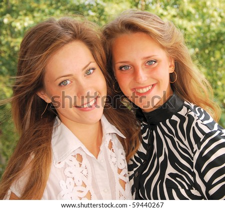 young pretty girlfriends over nature background - stock photo