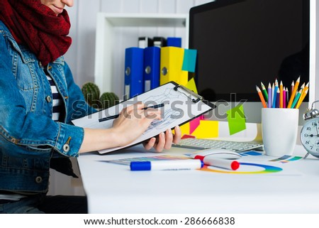 Young pretty Graphic designer using graphics tablet to do her work at desk - stock photo