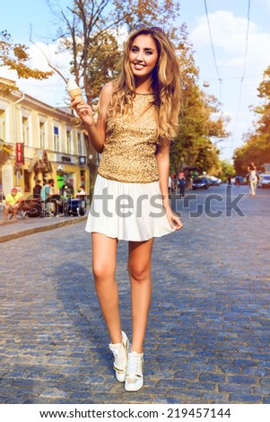 Young pretty happy girl in stylish golden top and white skirt, walking alone at european city center,eating her favorite vanilla tasty ice-cream, enjoy fall autumn sunny day. - stock photo