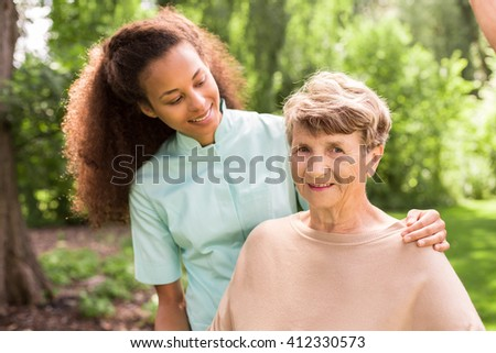 Young pretty helpful carer and senior woman