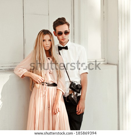 Young pretty hipster couple posing outdoor near white wall in summer on the street. Handsome brunette man and beautiful blonde woman vintage style dressed having fun outdoor together. - stock photo