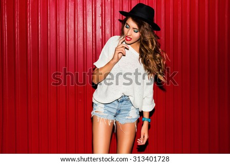 Young  pretty  hipster woman in trendy autumn clothes have fun and doing grimaces  near red  background  urban style  on  night party.  Bright flash ,  contrast color .  Wearing black hat. - stock photo
