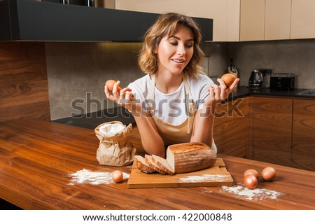 Young pretty housewife in the kitchen near the tableboard