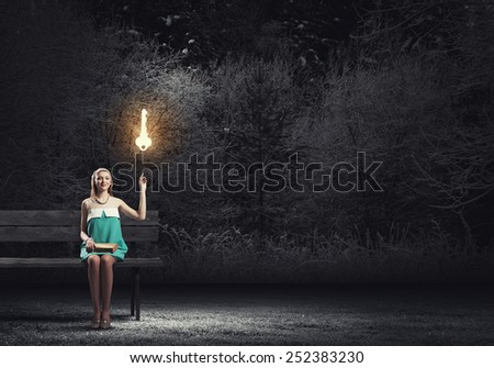 Young pretty lady sitting on bench with book in hands - stock photo