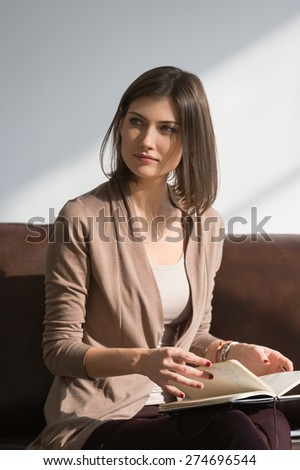 Young pretty lady sitting on couch at home or office thinking about something and planning - stock photo