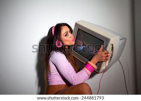 Young Pretty Latino Woman sitting in a hotel room lifting a vintage television set above her head