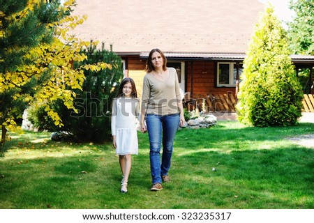 Young pretty mother and preteen age daughter outside at the beautiful sunny day