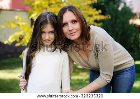 Young pretty mother and preteen age daughter outside at the beautiful sunny day - stock photo