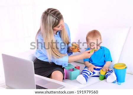 Young pretty mother feeding her son on sofa in room