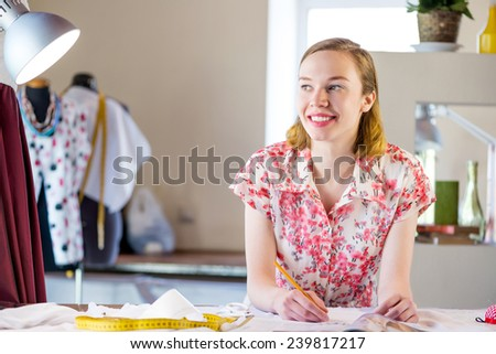 Young pretty needlewoman in studio working at order