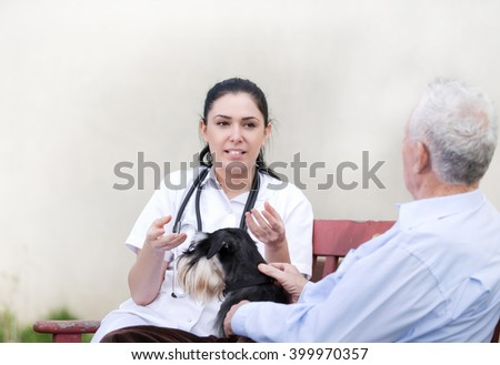 Young pretty nurse explaining something to senior man with dog on the bench in courtyard